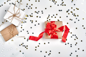 Present with red bow on white background with metallic star shaped confetti. Flat lay style
