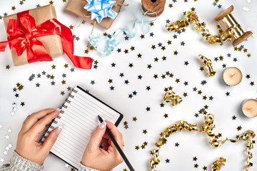 Festive decorations, delicate wavy ribbons, metallic star shaped confetti and notebook with wish list on white table, flat lay style. Christmas holidays decoration concept.