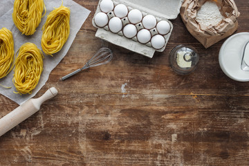 top view of uncooked pasta and raw ingredients on wooden table