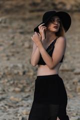 Sensual woman standing on stony ground