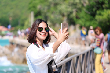 Hipster young girl standing on the bridge and taking selfie with smartphone tropical beach of the mountains background, Koh Larn in Pattaya city, Chonburi Thailand, Travel lifestyle vacations concept