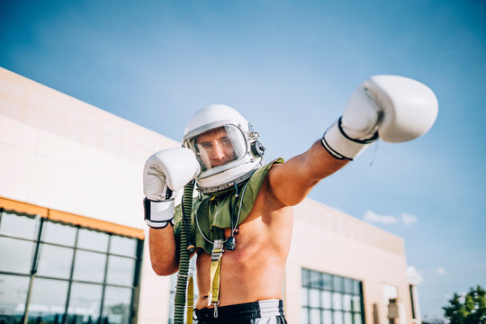 Man practicing boxing with astronaut helmet.