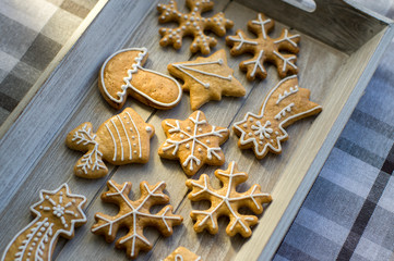 Painted traditional Christmas gingerbreads arranged on wooden tray in daylight, snowflakes and other Xmas symbols