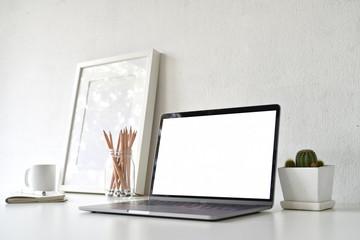 Workspace with blank white screen laptop on loft desk.