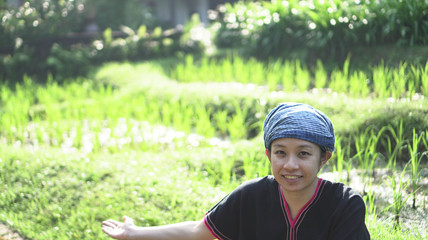 Asian ethnic woman with native dress smile at her organic rice field