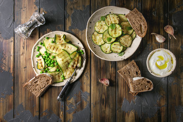Variety of grilled zucchini salad with green pea, yogurt dip, garlic and rye sliced bread in spotted ceramic plates over dark wooden plank background. Vegetarian food. Flat lay, space