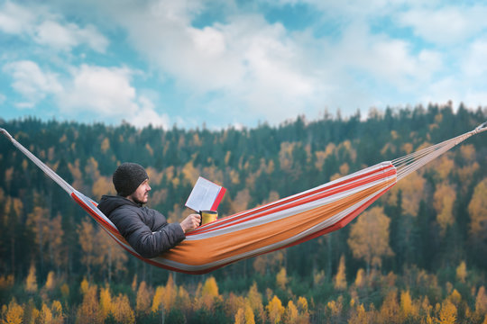 A man sits in a hammock and reads a book in a picturesque place. Mug in his right hand.
