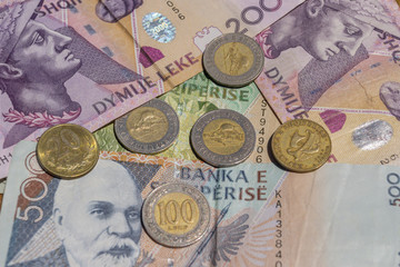 Albanian coins and banknotes on the beach.