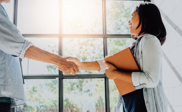 Business people shaking hands - businesswoman making handshake with a businessman.