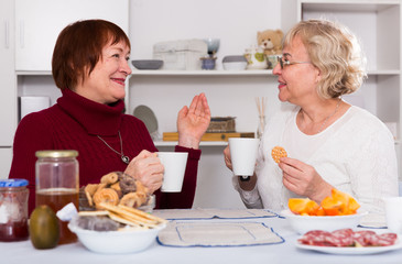 cheerful mature females talking and drinking tea
