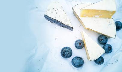 Разный сыр с плесенью и голубикой на бумажном фоне.