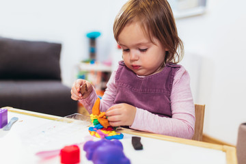 Kid girl is playing with plasticine while sitting at table in nursery room.