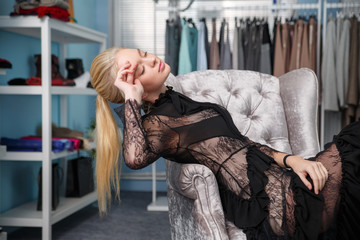 Beautiful blonde girl in a black lace dress in the store.