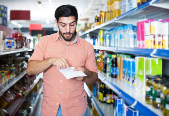 Portrait of man customer who is standing with note list in supermarket.