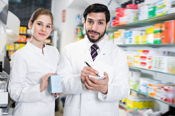 Two pharmacists are inventorying medicines with note near shelves in apothecary.