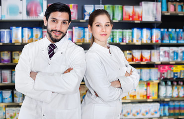 Portrait of two specialistes who are standing near shelves with medicines in pharmacy.