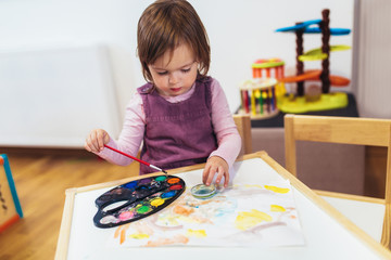 Cute happy little girl, preschooler, painting with water color