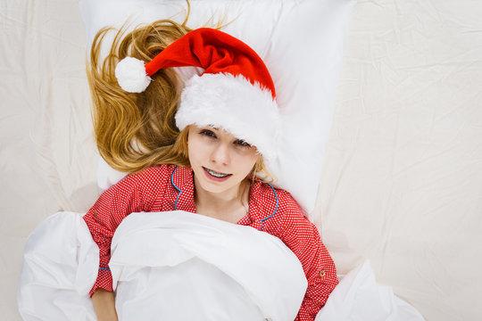 Happy woman wearing pajamas and Santa Claus hat
