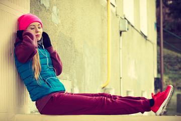 Woman wearing warm sportswear relaxing after exercising