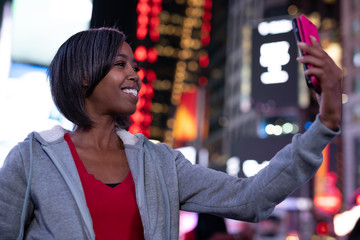 Woman in city at night taking selfie picture