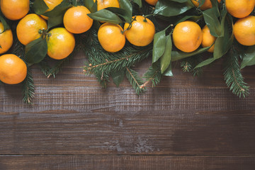 Fresh mandarins with leaves on wooden board. Christmas composition with copy space.