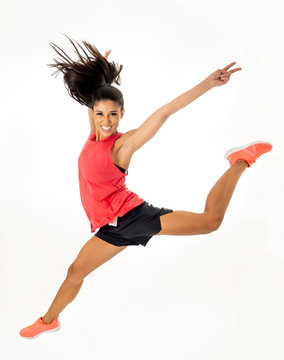Attractive excited fitness modern dancer girl in sport wear jumping of joy dancing and working out