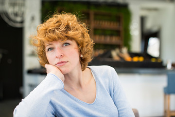 Portrait of red hair woman sitting in cafe and looking on the side