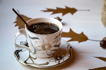 A cup of coffee on a white wooden table, and decoration by oak autumn leaves.
