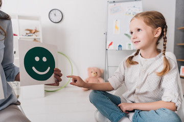 adorable little child pointing at smiley face on paper in hand of psychologist