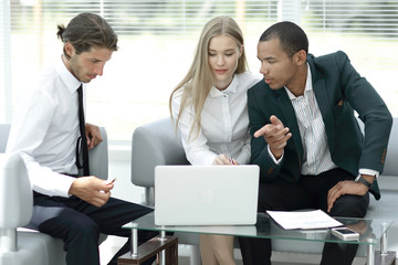 business team discussing information with a laptop