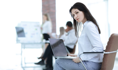 smiling business woman with laptop on blurred background