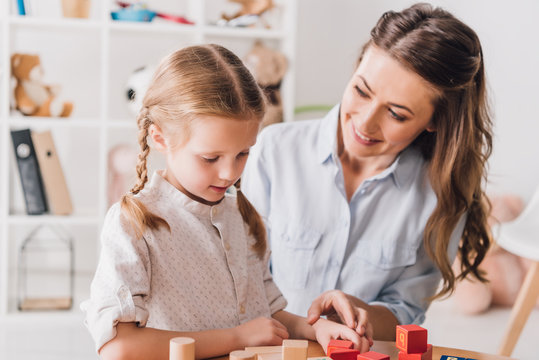 happy mother playing blocks with little child