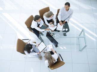Business team working with papers, view from above