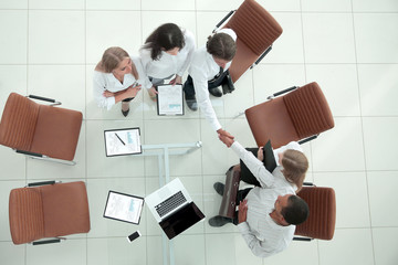 top view.handshake financial partners before the business meeting