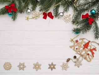 Christmas fir tree with decoration and glitters on wooden background. Christmas background on the white wooden desk