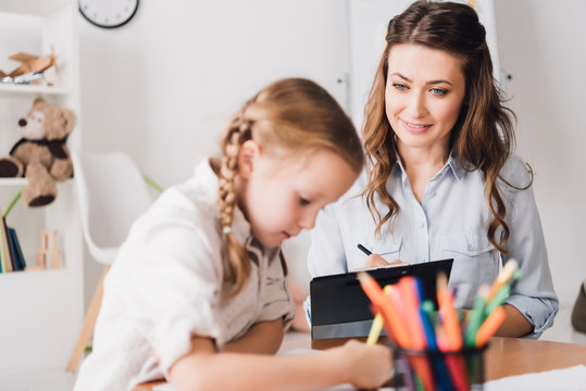 adult psychologist writing in clipboard while looking at little drawing child