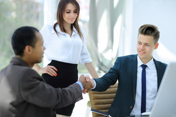 handshake of business partners sitting at a Desk