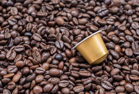 Modern coffee capsule on the roasted coffee bean.