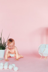 Happy Baby. Image of sweet baby boy, closeup portrait of child, cute toddler. Children, people, infancy and age concept. Infant child baby in diaper lying happy smiling on a pink background