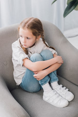 high angle view of lonely little child sitting in armchair and looking away