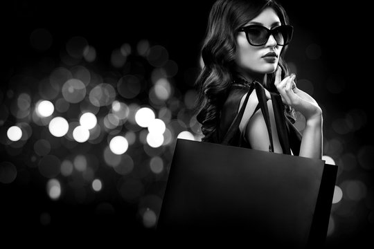 Christmas or Black friday sale concept. Shopping woman holding bag on dark background with bokeh in holiday. BW photo.