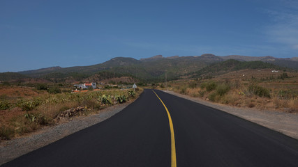 Empty road through Arona Municipality, surrounded by vineyards, terraced farms and wild endemic flora, view towards Teide National Park with the largest volcano in Spain, in Tenerife, Canary Islands