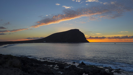 Early sunrise over Montana Roja, an unusual, stratovolcanic cone and La Tejita beach, one of the longest, natural beaches in Tenerife, Canary Islands, Spain. Panoramic perspective with natural light