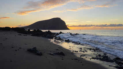Dramatic sunrise over Montana Roja an unusual, stratovolcanic cone and La Tejita beach, one of the longest, natural beaches in Tenerife, Canary Islands, Spain. Panoramic perspective with natural light
