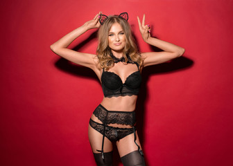 Young sexy girl in the image of a cat in black lingerie on a red background