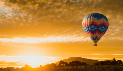 hot air balloon flying at yellow sunrise
