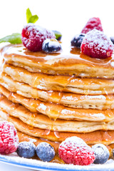 Pile of pancakes with blueberries and raspberries sprinkled with icing sugar and poured on with honey
