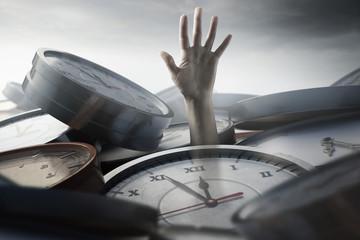 Person unter Zeitdruck steckt zwischen Uhren fest