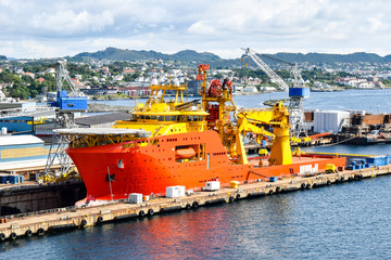 A large orange and yellow colored Offshore Construction Vessel (OCV) is in a dry dock of a shipyard and is being repaired