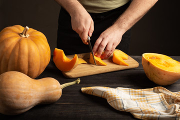 The cook slices the pumpkin for baking.